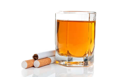 tipple: glass of cognac and cigarettes isolated on a white background