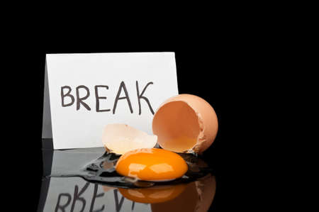 Break Time and broken egg isolated on a black background photo