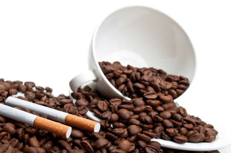full cup with coffee beans and cigarettes isolated on a white background