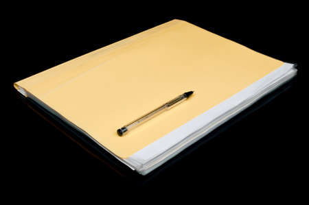 yellow folder and pen isolated on a black background photo