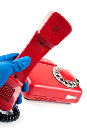 man in blue gloves picked it up the red phone isolated on a white background photo