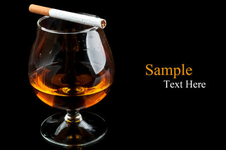 cognac with cigarettes in a classic glass isolated on a black background