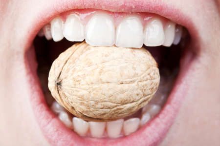 a woman with a healthy and beautiful teeth eating hard nut photo