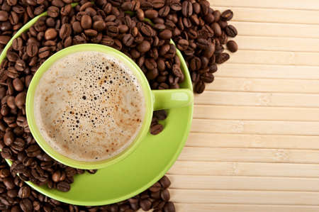 hot green cup of cappuccino with coffee beans background Stock Photo