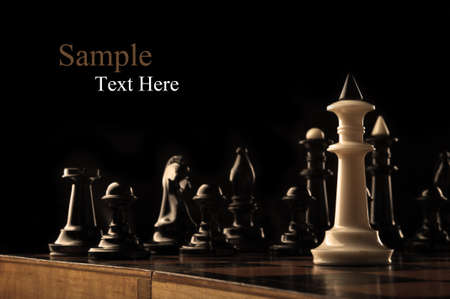a white king of chess against the black pieces photo