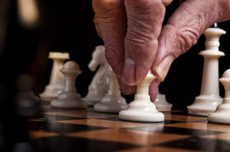 man plays chess and makes the first move a pawn photo