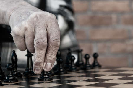 old man playing chess and makes the first move a pawn Stock Photo - 13508004