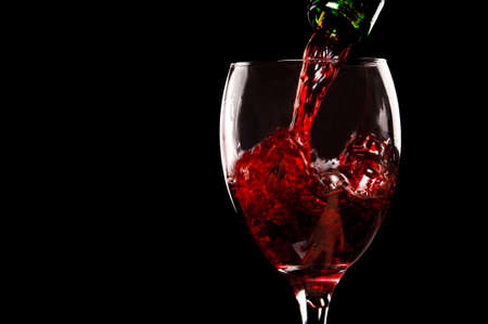 pouring red wine isolated on a black background Stock Photo