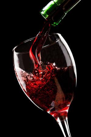 botella de licor: verter el vino rojo aislado en un fondo negro