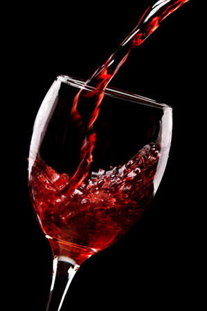 red wine pouring into wine glass isolated on a black background