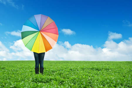 girl with colorful umbrella in field photo