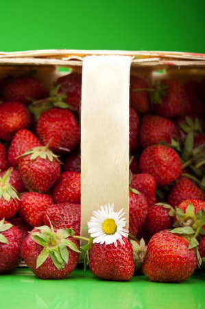 fresh strawberry in basket on green background photo