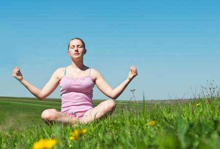 girl meditates in green grass background photo