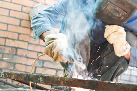 man welding in workshop with safety precaution
