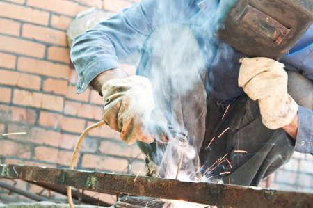 man welding in workshop with safety precaution