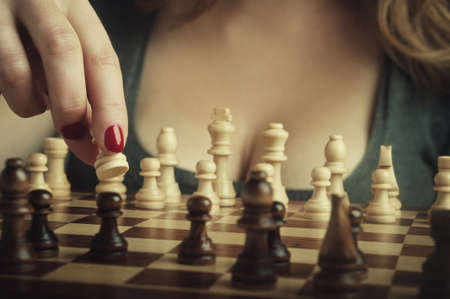 sexy woman playing chess and hold pawn Stock Photo - 17299029