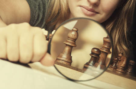 woman play chess and hold loupe background photo