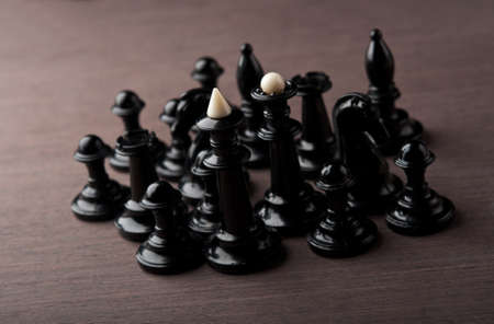 black chess pieces on a wooden table photo