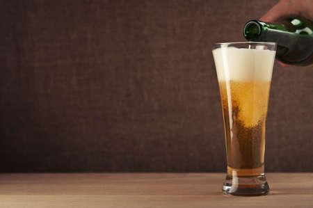 hombre tomando cerveza: hombre que vierte cerveza en el vaso