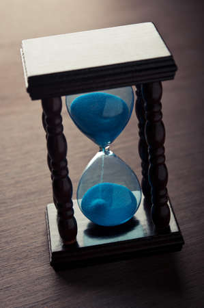 hourglass clock on wooden table photo