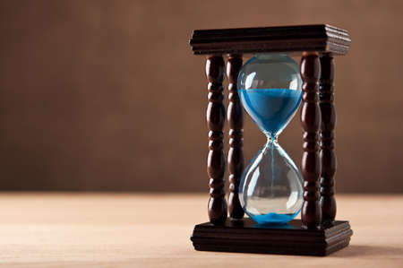 sands of time: hourglass on wooden table Stock Photo