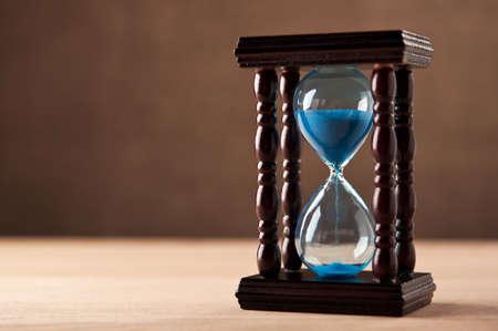 reloj de arena: reloj de arena sobre tabla de madera Foto de archivo