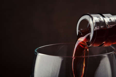 pouring red wine on background