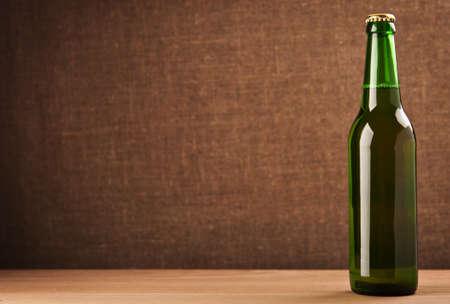 green beer bottle on old background photo