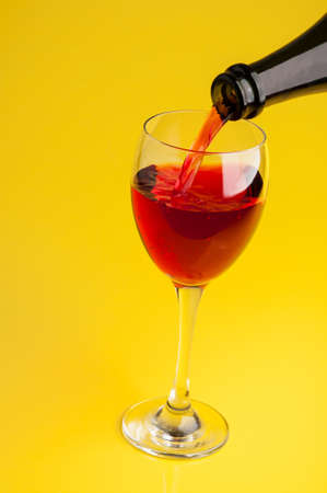 Pouring red wine into a glass on a yellow background photo