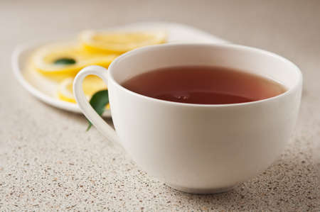 hot cup of tea with lemon in kitchen table photo