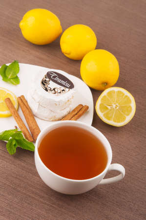 Cup of tea with cake and lemons photo