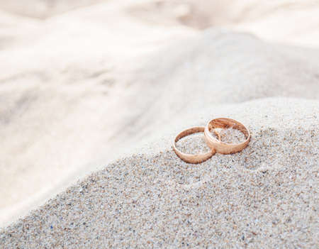 Closeup of wedding rings on beach