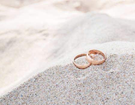 hochzeit: Nahaufnahme der Hochzeitsringe auf Strand