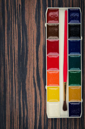 paints palette on wooden background photo
