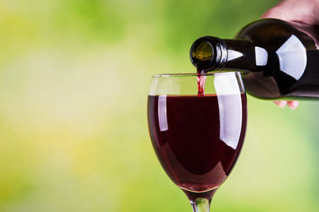 red wine glass: Woman pouring red wine into glass Stock Photo