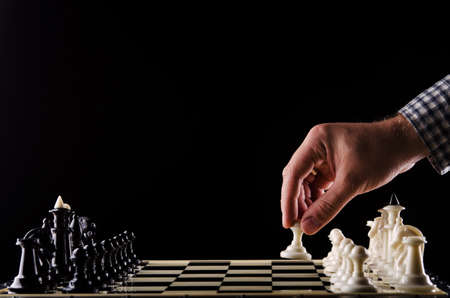 first move: man plays chess and makes the first move a pawn Stock Photo