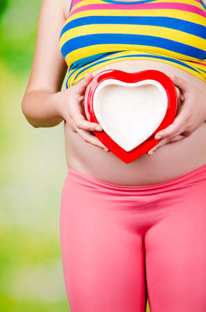 pregnant woman holding red heart on green background photo