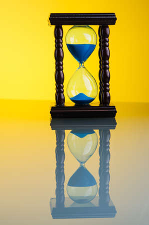 hourglass clock on yellow glass background photo