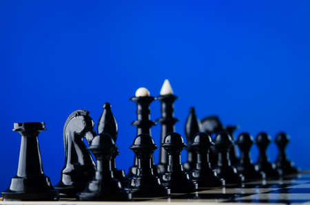 chess pieces on board blue background photo