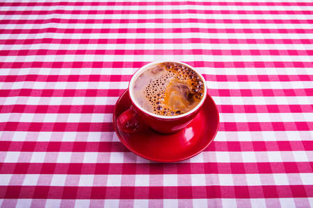 red coffee cup on table in kitchen photo