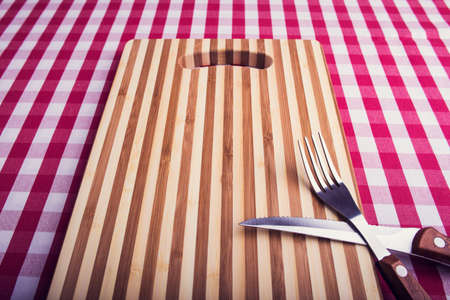 Cutting board on kitchen table photo