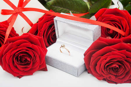 Love background. Rose flowers, gift box with red ribbon and diamond ring. photo
