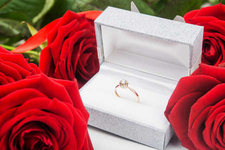 Red roses and ring with diamond on background photo