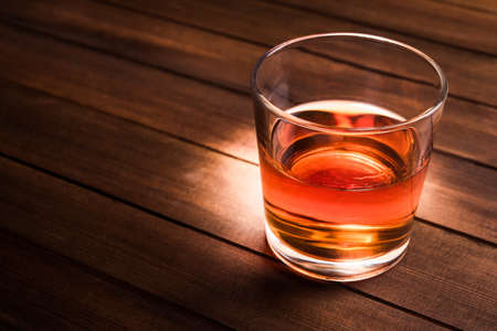 Glass with cognac on wood table photo