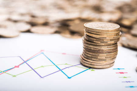 Stack of coins and graph on background photo