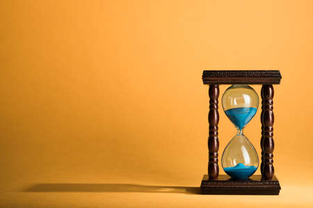 clock: Hourglass clock on yellow vintage background Stock Photo