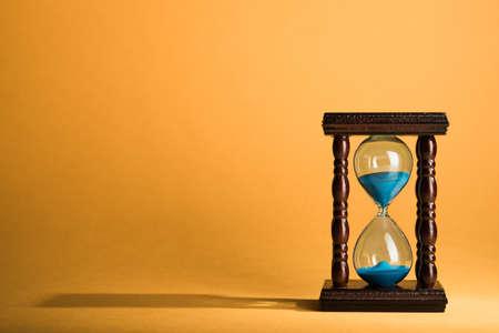 reloj de arena: Reloj reloj de arena en el fondo amarillo de la vendimia Foto de archivo