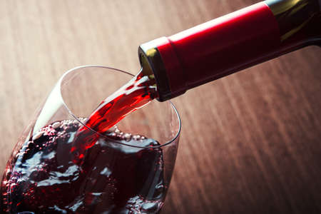 Closeup of red wine pouring in glass