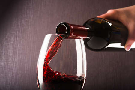 pouring wine: Poured red wine into glass