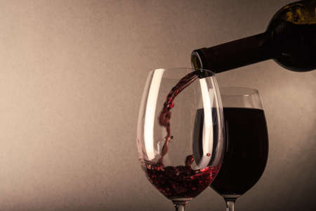 Red wine poured into a glass on background
